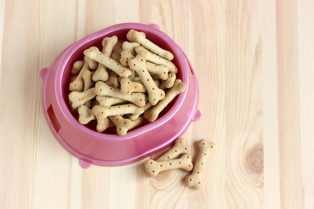 Biscotti a forma di osso in una ciotola di plastica rosa