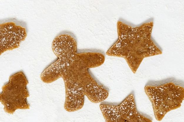 Biscotti a forma di pan di zenzero, albero di natale, stelle, campana su carta per cottura