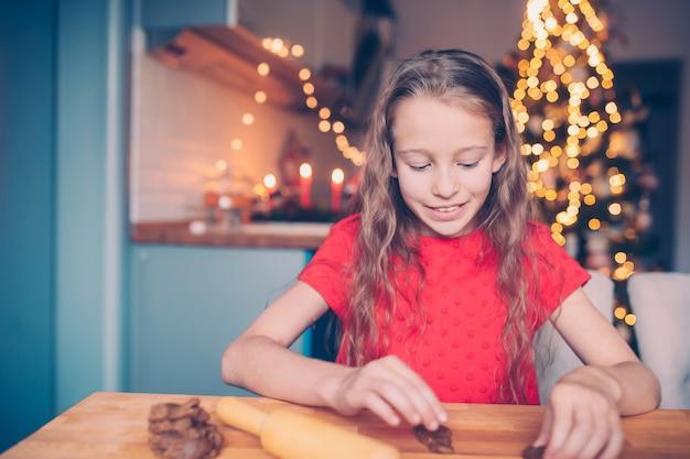 Biscotti adorabili del pan di zenzero di natale di cottura della bambina