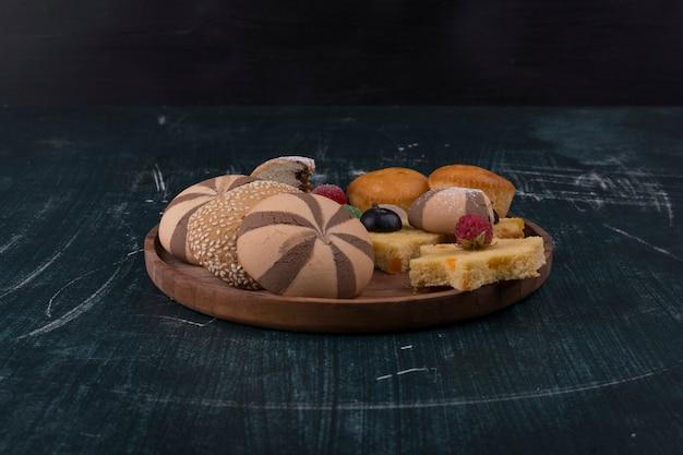 Biscotti al cacao e focacce con frutti di bosco su un piatto di legno sul nero