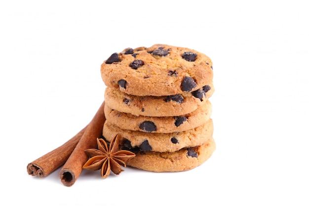 Biscotti al cioccolato con bastoncini di cannella e anice stellato isolato su sfondo bianco.