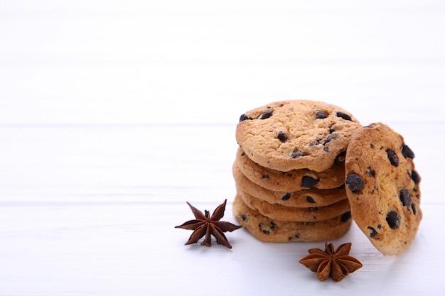 Biscotti al cioccolato con bastoncini di cannella e anice stellato su sfondo bianco.