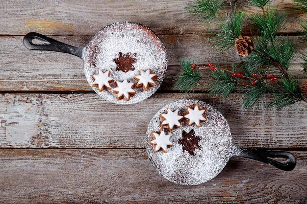 Biscotti al cioccolato con i biscotti della stella, rami di abete sulla tavola di legno