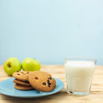 Biscotti al cioccolato con latte e mele sul tavolo