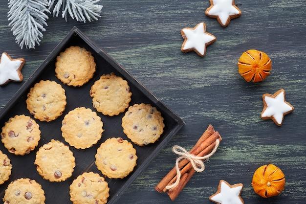 Biscotti al cioccolato di natale, piatto con spezie e decorazioni invernali sul buio