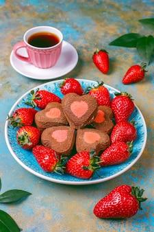 Biscotti al cioccolato e fragola a forma di cuore con fragole fresche