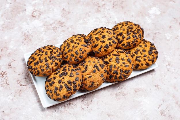 Biscotti al cioccolato in stile americano su sfondo di cemento chiaro.