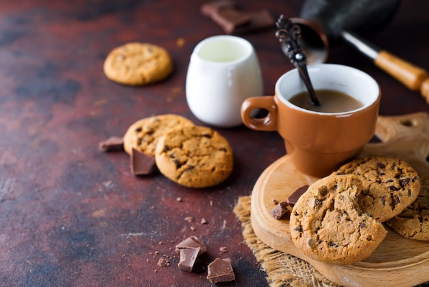 Biscotti al cioccolato nel piatto e tazza di caffè caldo