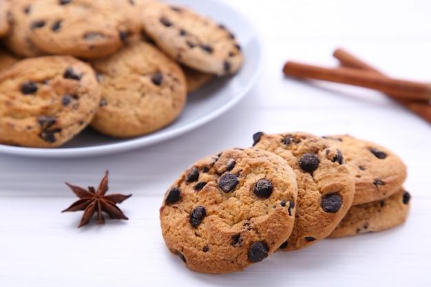 Biscotti al cioccolato sul piatto su bianco in legno