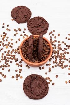 Biscotti al cioccolato vista dall'alto con chicchi di caffè sulla superficie bianca