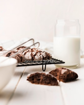 Biscotti al cioccolato vista frontale con latte sul tavolo