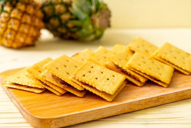 Biscotti al formaggio con marmellata di ananas su legno