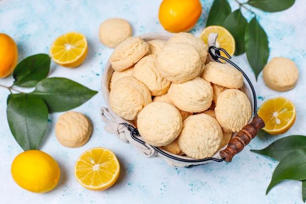 Biscotti al limone fatti in casa con limoni sulla superficie della luce
