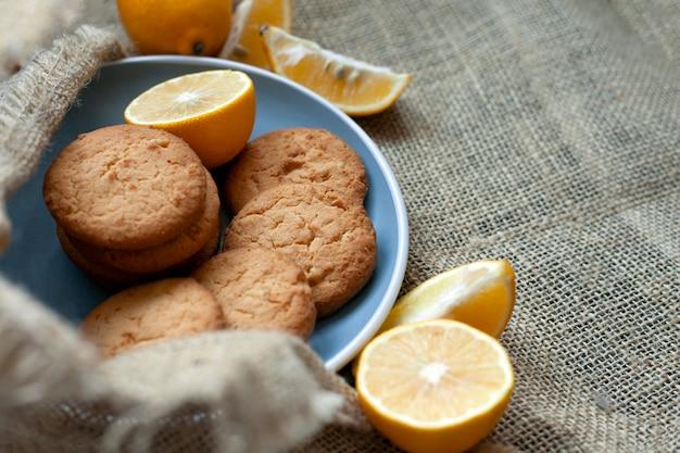 Biscotti al limone fatti in casa, la cottura degli agrumi si trova deliziosamente su un piatto nel tessuto, vista dall'alto