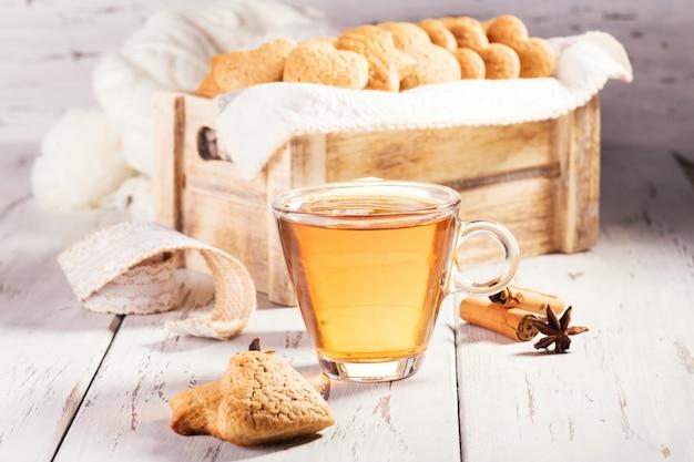 Biscotti allo zenzero a forma di cuore biscotti su un tavolo di legno naturale malandato con una tazza di tè.