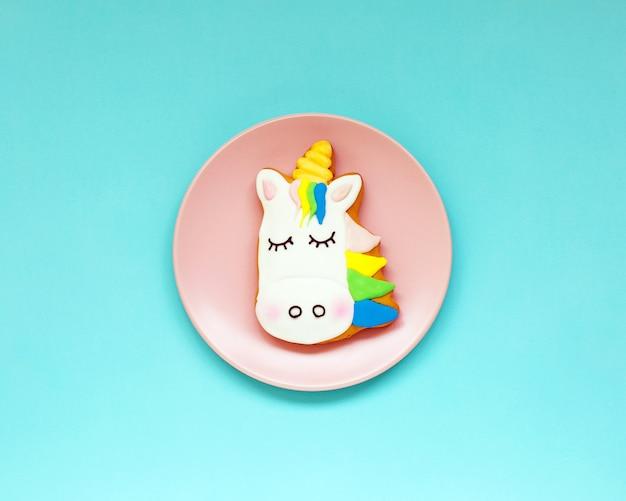 Biscotti allo zenzero a forma di un unicorno su carta pastello geometrica