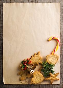 Biscotti allo zenzero di natale con rami di abete sulla carta da imballaggio.
