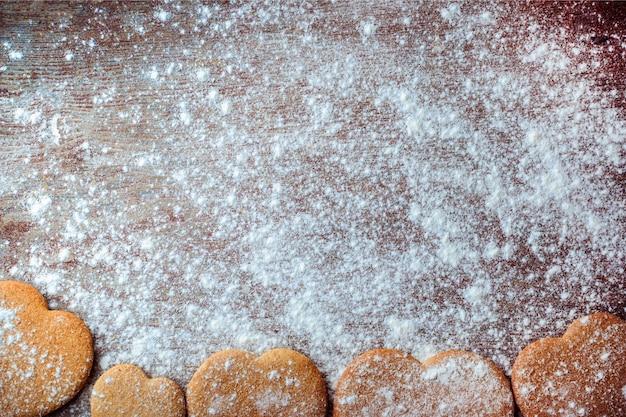 Biscotti allo zenzero sotto forma di cuori su una tavola di legno cosparsa di farina.