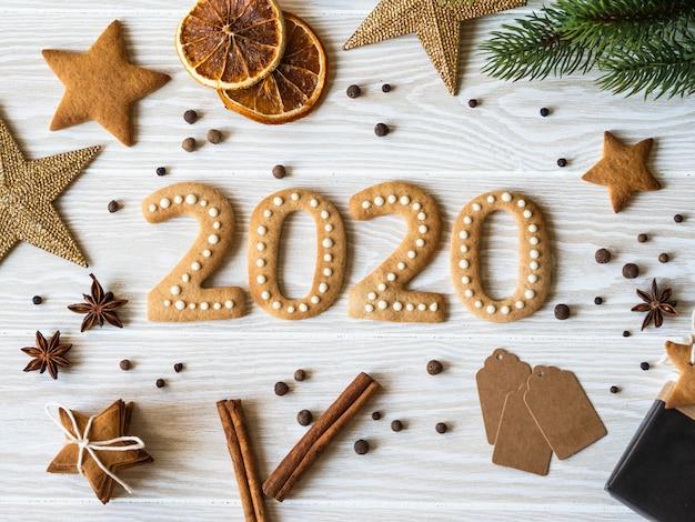 Biscotti allo zenzero sotto forma di numeri e biscotti allo zenzero del 2020 con legno bianco. vista dall'alto. imballaggi stagionali, spezie e attributi di capodanno
