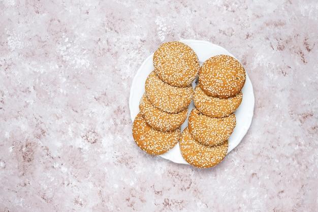 Biscotti americani dei semi di sesamo su fondo in cemento leggero.
