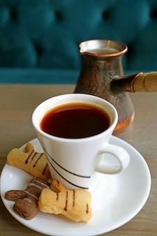 Biscotti caldi di burro e del caffè turco con la caldaia vaga del caffè nel fondo