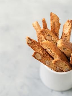 Biscotti (cantuccini) - dessert di mandorla italiano tradizionale in primo piano bianco della tazza.