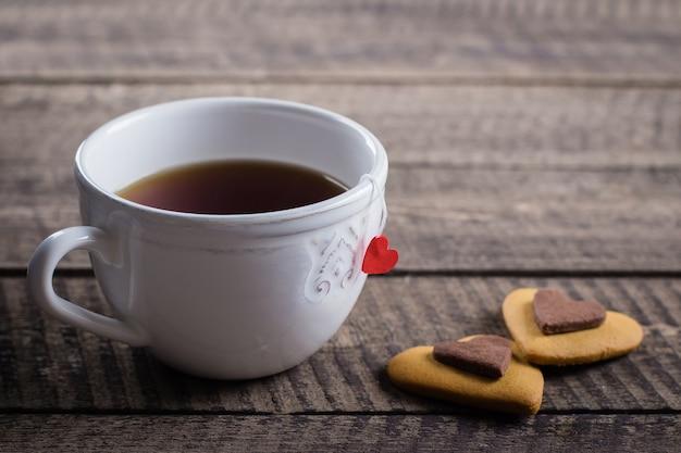 Biscotti casalinghi cuore e tazza di tè per san valentino sul fondo della tavola in legno