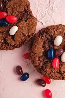 Biscotti casalinghi del cioccolato dell'avena con cereale con i fagioli di gelatina succosi sulla superficie rosa, macro di vista superiore