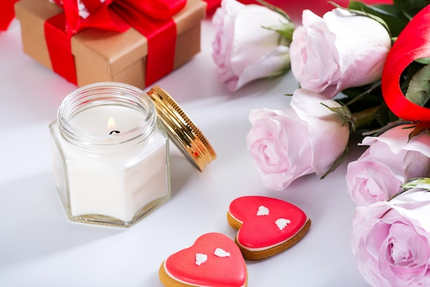 Biscotti casalinghi del cuore di giorno di biglietti di s. valentino, rose rosa e candela sulla tavola bianca