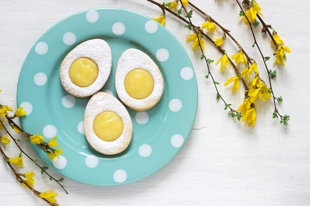 Biscotti casalinghi del limone di pasqua e ramoscelli di fioritura di forsythia su un fondo leggero.