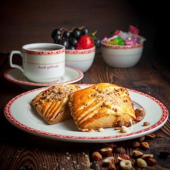 Biscotti casalinghi del primo piano con la tazza di tè e le caramelle sulla tavola di legno