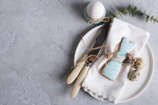 Biscotti casalinghi di pasqua sotto forma di un coniglio divertente sul piatto bianco. regolazione festiva della tavola di pasqua. decorazioni natalizie.