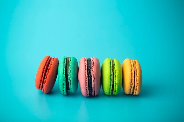 Biscotti colorati del maccherone (macarons) su un fondo blu. brillanti pasticcini festivi, dessert e dolci. sfondo di cottura