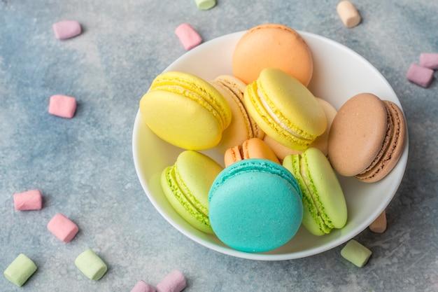 Biscotti colorati macarons sul piatto e marshmallow ariosi