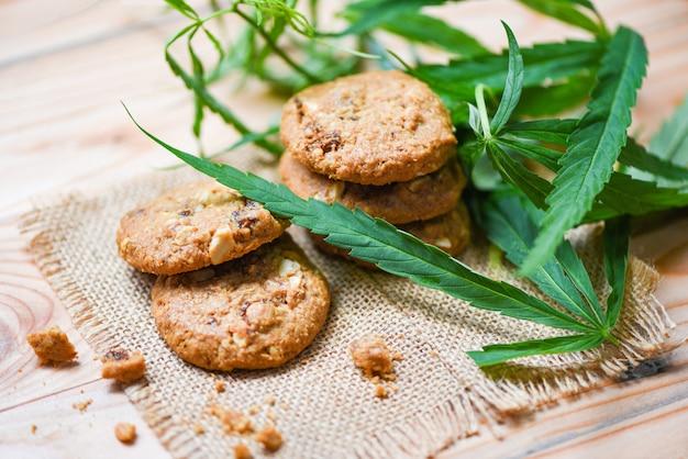 Biscotti con cannabis foglia di marijuana erba sul sacco in legno - spuntino di cannabis cibo per la salute