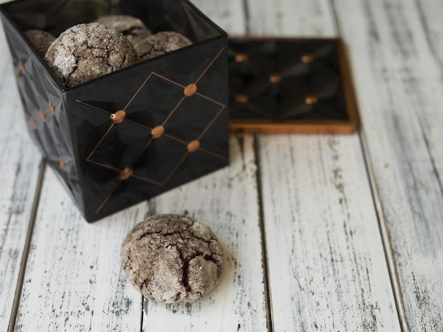 Biscotti con gocce di cioccolato, crepe, scatola vintage nero con biscotti su sfondo bianco.