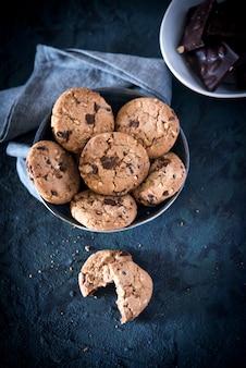 Biscotti con gocce di cioccolato e nocciole, fatti con farina d'avena e farina di frumento.