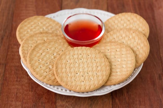Biscotti con inceppamento sul piatto su fondo marrone