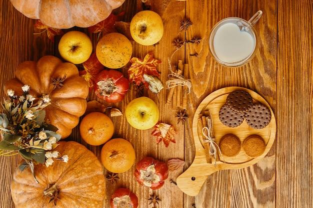 Biscotti con latte sul tavolo. biscotti di zucca sul tavolo di legno con zucche
