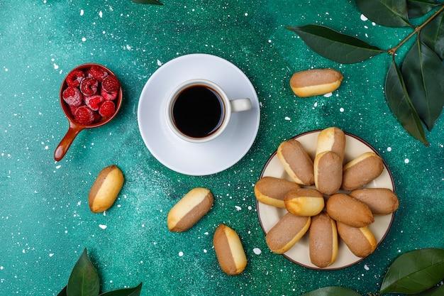 Biscotti con ripieno di marmellata di lamponi e lamponi congelati su sfondo chiaro
