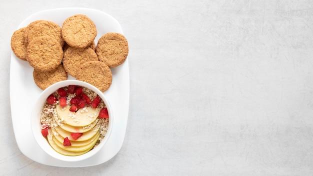 Biscotti copia-spazio e ciotola con cereali e frutta