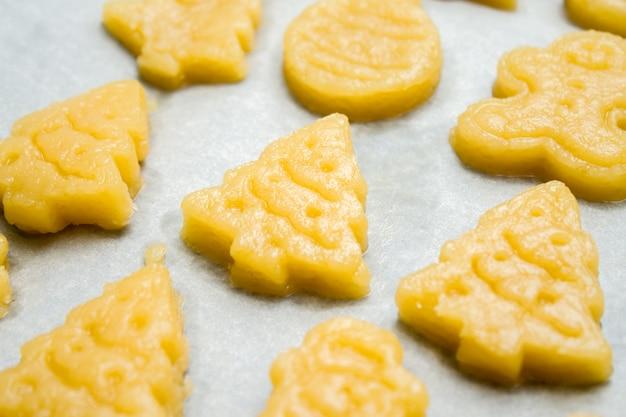 Biscotti crudi di natale del pan di zenzero della pasta per childrenin sotto forma di palla, abete, pupazzo di neve