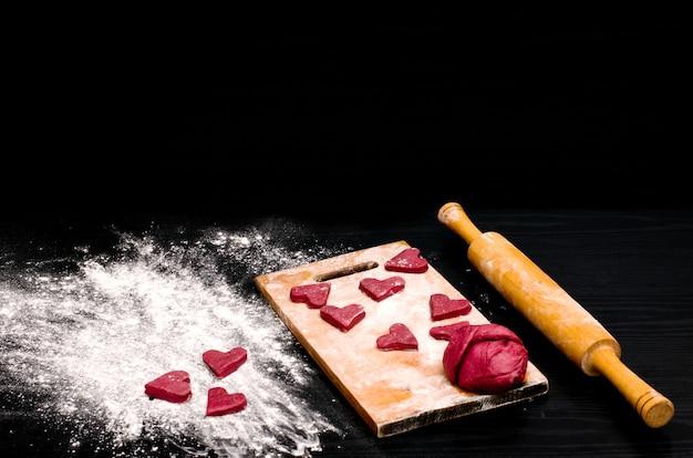 Biscotti cuore rosso su un tavolo nero, cottura per san valentino