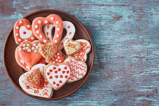 Biscotti decorati di forma del cuore in piatto su gray