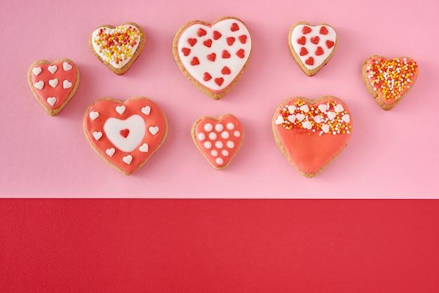 Biscotti decorati di forma del cuore su fondo rosa