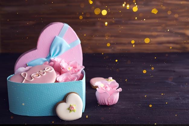 Biscotti dei cuori in scatola blu del cuore con rosa su fondo di legno scuro, spazio della copia