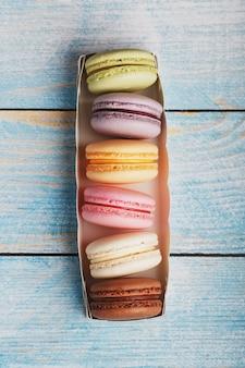 Biscotti dei maccheroni dei colori differenti in una scatola su un fondo di legno blu e vecchio di colore blu.