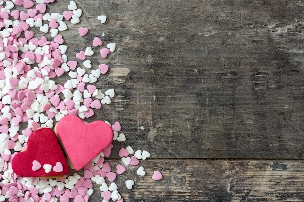 Biscotti del biglietto di s. valentino con forma del cuore su superficie di legno