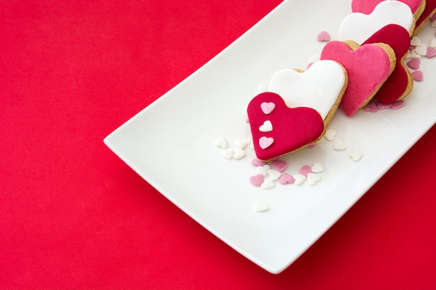 Biscotti del biglietto di s. valentino con forma del cuore su superficie rossa