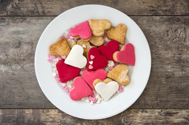 Biscotti del biglietto di s. valentino con forma del cuore sulla vista superiore della superficie di legno